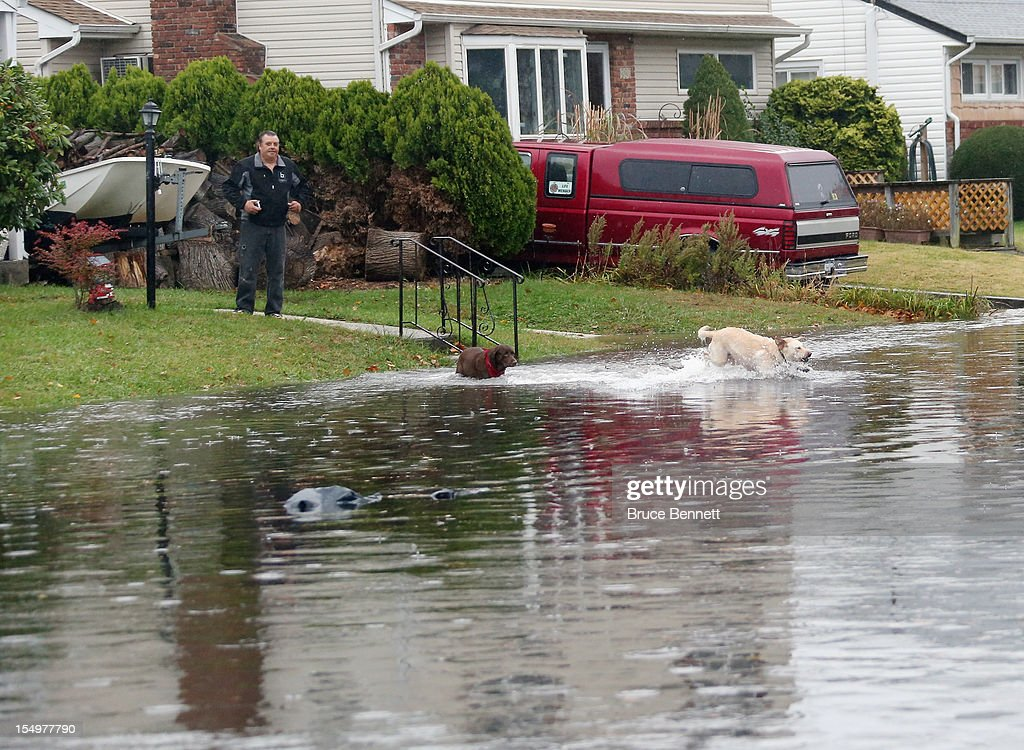 Jerry Smith of South Long Beach Avenue watches his dogs take a dip in the flooded street in front of his home as high tide and winds from Hurricane Sandy combine to flood the area on October 29, 2012 in Freeport, New York. The storm, which threatens 50 million people in the eastern third of the U.S., is expected to bring days of rain, high winds and possibly heavy snow.
