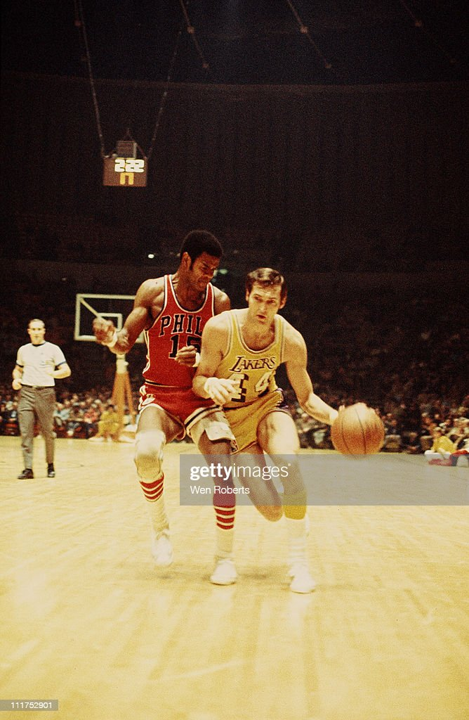 Jerry West of the Los Angeles Lakers dribbles against Hal Greer of the Philadelphia 76ers at the Great Western Forum in Inglewood California circa...