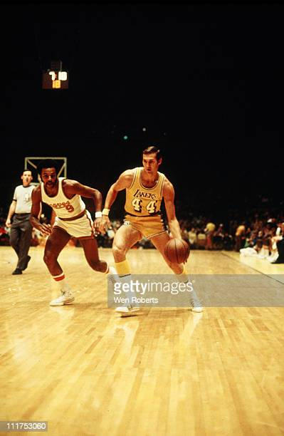 Jerry West of the Los Angeles Lakers dribbles against Herm Gilliam of the Buffalo Braves at the Great Western Forum in Inglewood California circa...