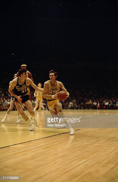 Jerry West of the Los Angeles Lakers dribbles against Pete Cross of the Seattle Supersonics at the Great Western Forum in Inglewood California circa...