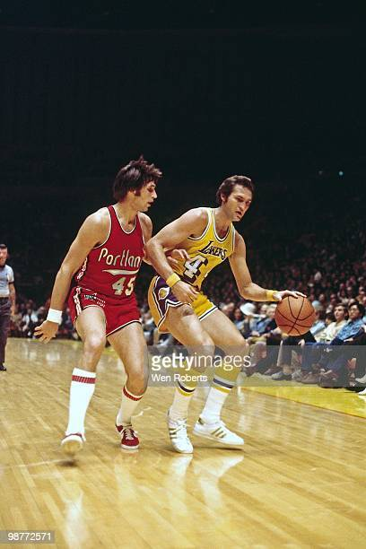 Jerry West of the Los Angeles Lakers moves the ball up court against Geoff Petrie of the Portland Trail Blazers during a game played circa 1971 at...