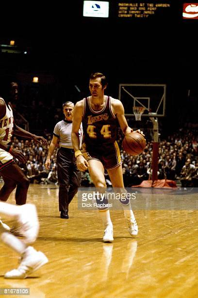 Jerry West of the Los Angeles Lakers moves the ball up court during a game circa 1970 against the New York Knicks at Madison Square Garden in New...