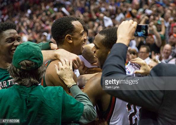 Jerryd Bayless center with head band of the Milwaukee Bucks is swarmed by teammates John Henson left and Khris Middleton right after he hit the game...