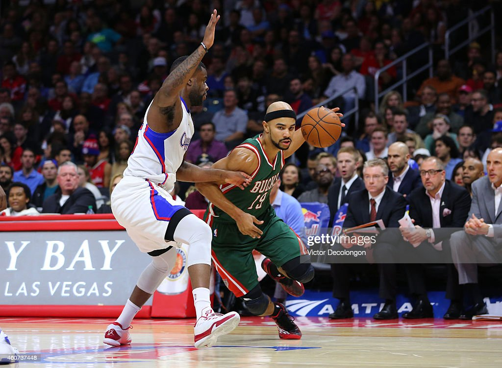 Jerryd Bayless #19 of the Milwaukee Bucks drives against Reggie Bullock #25 of the Los Angeles Clippers in the first half during the NBA game at Staples Center on December 20, 2014 in Los Angeles, California.