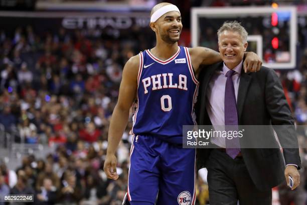 Jerryd Bayless of the Philadelphia 76ers talks with head coach Brett Brown in the second half against the Washington Wizards at Capital One Arena on...
