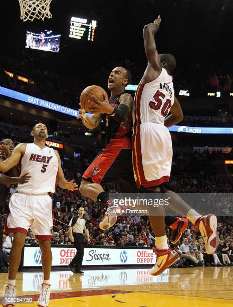 Jerryd Bayless of the Toronto Raptors goes up for a shot against Joel Anthony of the Miami Heat during a game at American Airlines Arena on January...
