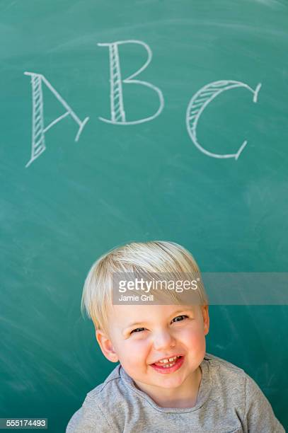 Jersey City, Boy (2-3) smiling in front of blackboard with letters ABC written on it