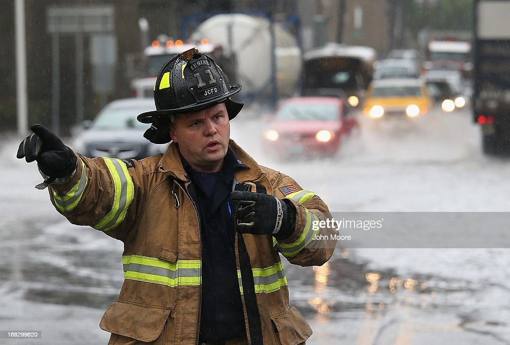 A Jersey City firefighter directs traffic away from a flooded underpass on May 8, 2013 in Jersey City, New Jersey. Heavy rains flooded streets, stranding some motorists during morning rush hour traffic.