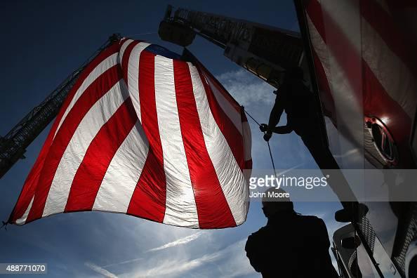 Jersey City firemen raise a flag from ladder trucks at Liberty State Park on September 17 2015 in Jersey City New Jersey The group representing 30...