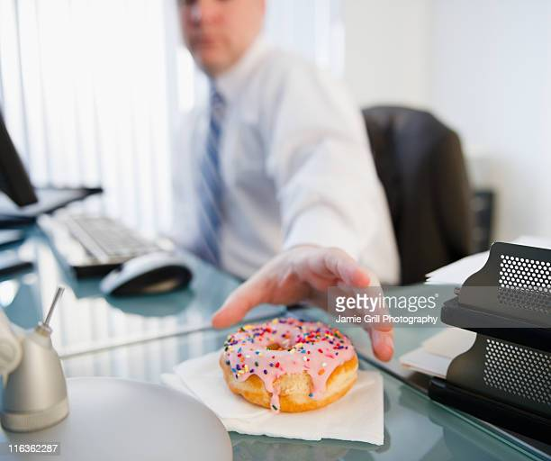 USA, Jersey City, New Jersey, businessman reaching for donut