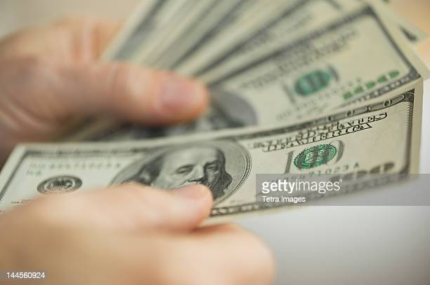 Jersey City, New Jersey, Close up of man's hands counting dollar banknotes