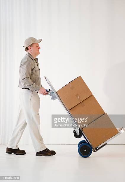 USA, Jersey City, New Jersey, delivery man pushing hand truck