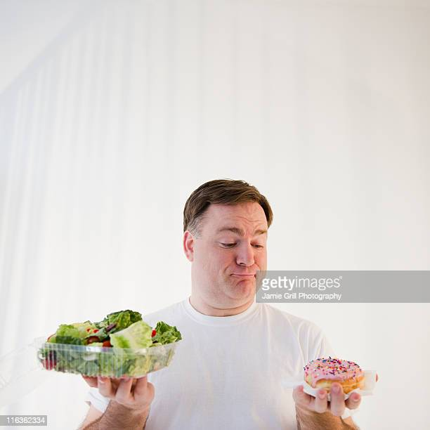 USA, Jersey City, New Jersey, man comparing donut and salad