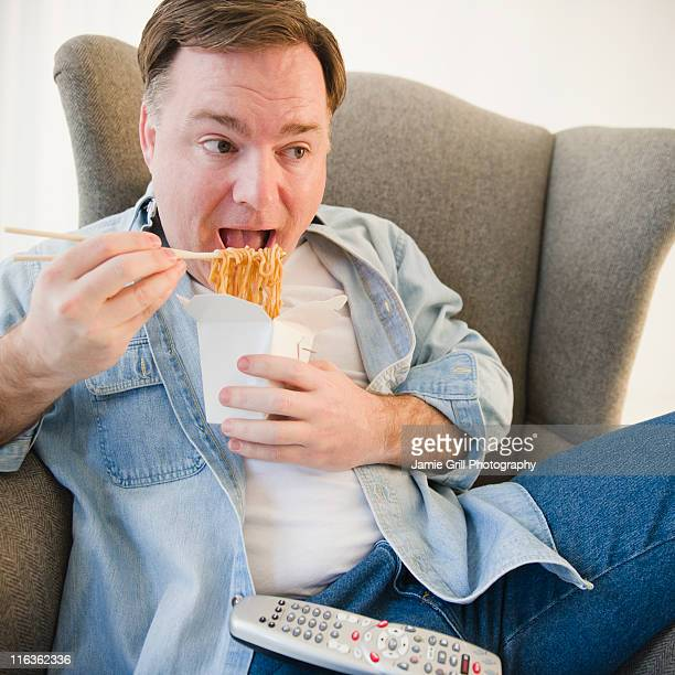 USA, Jersey City, New Jersey, man eating noodles
