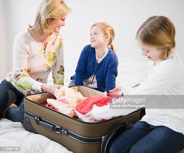 USA, Jersey City, New Jersey, mother and daughters (8-11) packing suitcase