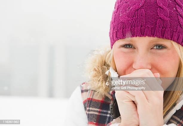 Jersey City, New Jersey, woman wearing warm clothing clasping hands