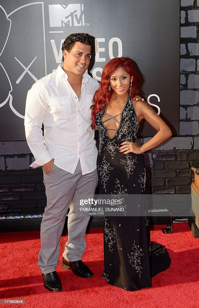 'Jersey Shore' star Nicole 'Snooki' Polizzi (Detail: NYC Glitz dress) (R) with husband Jionni LaValle (L) arrive at the MTV Video Music Awards August 25, 2013 at the Barclays Center in New York. AFP PHOTO / Emmanuel DUNAND