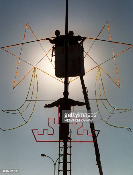 Jerusalem municipality workers hang Christmas stars on an electric pole in the main street of Jerusalem leading to the West Bank town of Bethlehem 30...