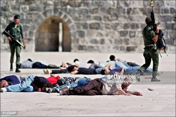 Israeli border policemen stand over arrested Palestinians 08 October 1990 following the serious rioting at the AlAqsa mosque compound in Jerusalem's...