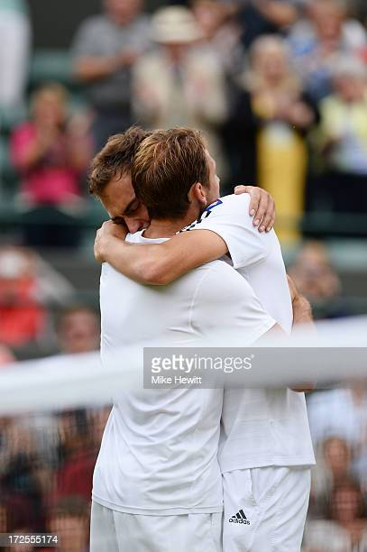 Jerzy Janowicz of Poland embraces Lukasz Kubot of Poland after their Gentlemen's Singles quarterfinal match against Lukasz Kubot of Poland on day...