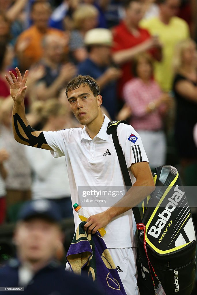 Jerzy Janowicz of Poland waves to the crowd as he walks off Centre Court following his defeat to Andy Murray of Great Britain in the Gentlemen's...