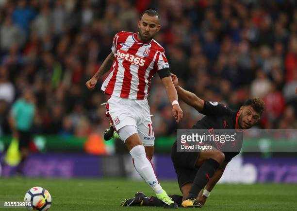 Jese of Stoke City and Alex OxladeChamberlain of Arsenal battle for possession during the Premier League match between Stoke City and Arsenal at...