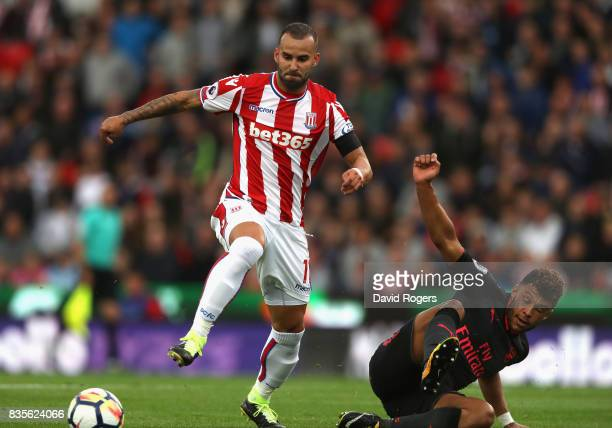 Jese of Stoke City is challenged by Alex OxladeChamberlain during the Premier League match between Stoke City and Arsenal at Bet365 Stadium on August...