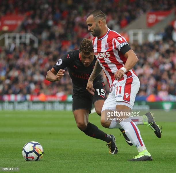 Jese of Stoke City runs with the ball past Alex OxladeChamberlain during the Premier League match between Stoke City and Arsenal at Bet365 Stadium on...