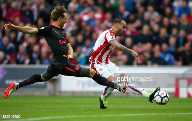 Jese of Stoke City scores his sides first goal as Nacho Monreal of Arsenal attempts to block during the Premier League match between Stoke City and...