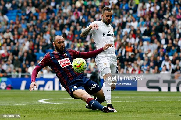 Jese Rodriguez of Real Madrid competes for the ball with Ivan Ramis of Eibar during the La Liga match between Real Madrid CF and SD Eibar at Estadio...