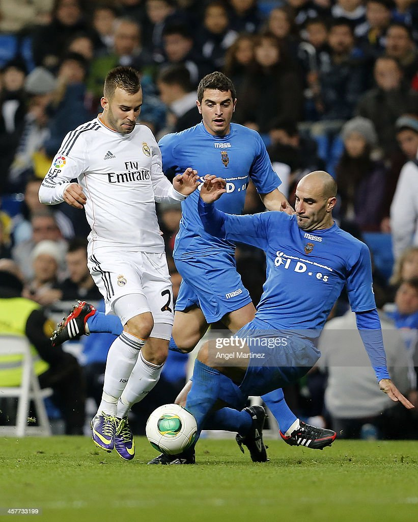 Jese Rodriguez of Real Madrid competes for the ball with Kike Alcazar of Olimpic de Xativa during the Copa del Rey, round of 32 match between Real Madrid and Olimpic de Xativa at Estadio Santiago Bernabeu on December 18, 2013 in Madrid, Spain.