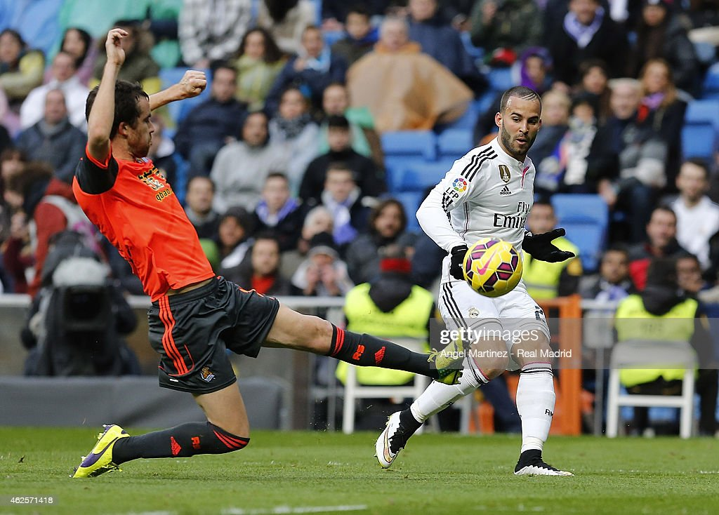 Jese Rodriguez of Real Madrid passes the ball under pressure from Mikel Gonzalez of Real Sociedad during the La Liga match between Real Madrid CF and...