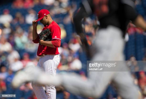 Jesen Therrien of the Philadelphia Phillies walks back to the mound after allowing a solo home run to Christian Yelich of the Miami Marlins in the...