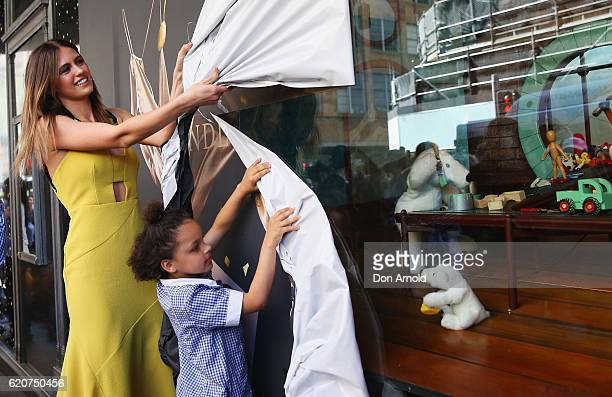 Jesinta Campbell and a school girl named Holly rip the paper off the windows during the David Jones Christmas Windows Launch at David Jones Elizabeth...