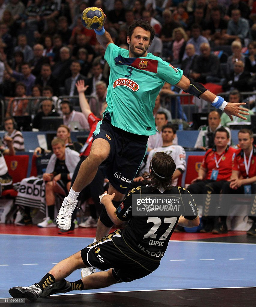 Jesper Brian Noeddesbo of Barcelona jumps over Ivan Cupic of Rhein Neckar during the EHF Final Four semi final match between RheinNeckar Loewen and...