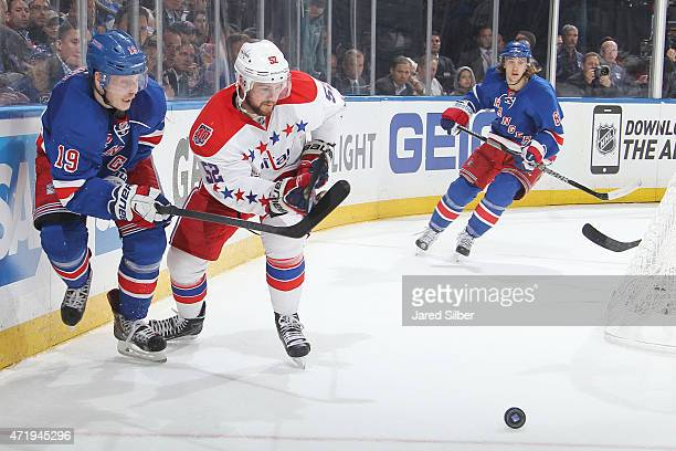 Jesper Fast of the New York Rangers and Mike Green of the Washington Capitals skate for the puck in Game One of the Eastern Conference Semifinals...