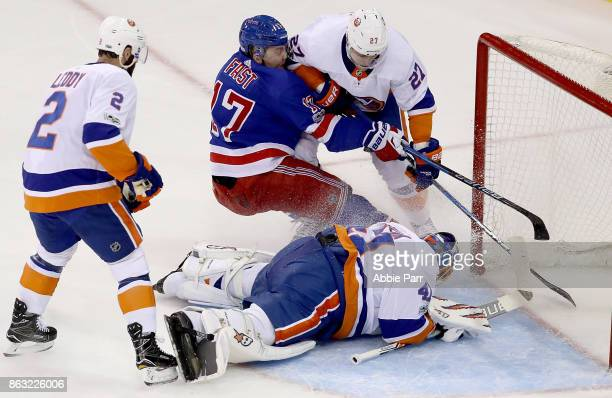 Jesper Fast of the New York Rangers takes a shot against Anders Lee of the New York Islanders in the first period at Madison Square Garden on October...