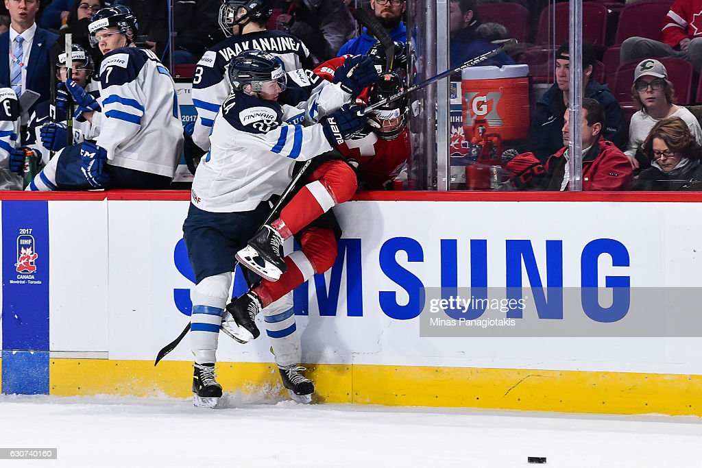 Jesper Mattila #28 of Team Finland checks Nando Eggenberger #22 of Team Switzerland into the stanchion during the 2017 IIHF World Junior Championship preliminary round game at the Bell Centre on December 31, 2016 in Montreal, Quebec, Canada. Team Finland defeated Team Switzerland 2-0.