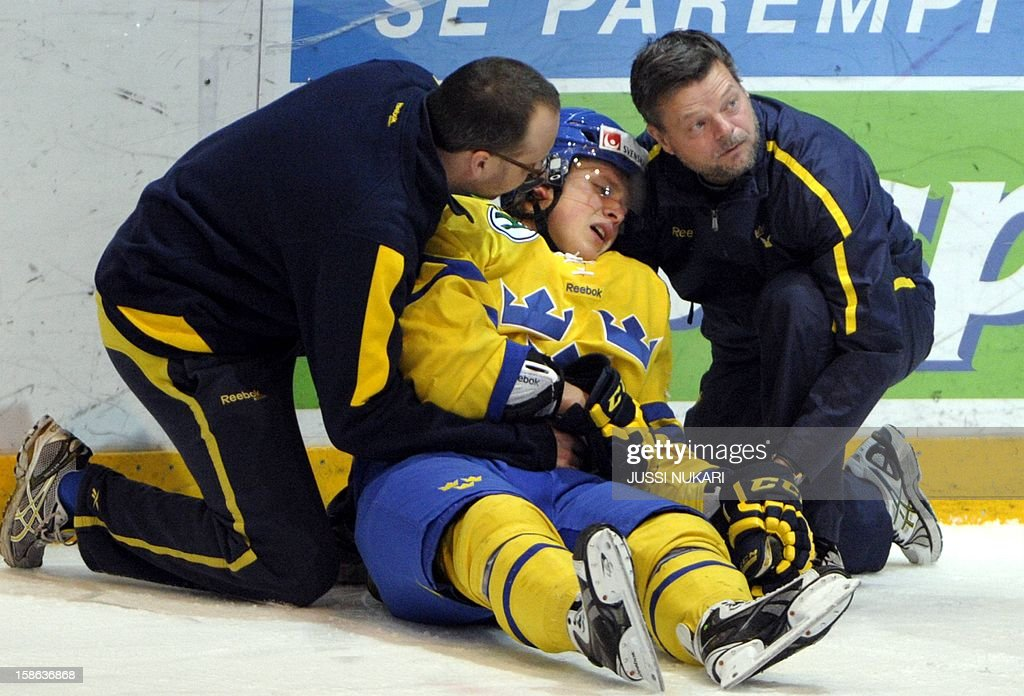 Jesper Pattersson (C) of Sweden gets badly hurt during the U20 Premiere WC ice hockey match Canada vs Sweden in Helsinki, (C) of Sweden gets badly hurt during the U20 Premiere WC ice hockey match Canada vs Sweden in Helsinki, Finland, December 22, 2012. AFP PHOTO / LEHTIKUVA / Jussi Nukari