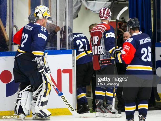 Jesper Williamsson of HV71 is helped off the ice after a highsticking by Victor Stancescu of Kloten Flyers during the Champions Hockey League group...