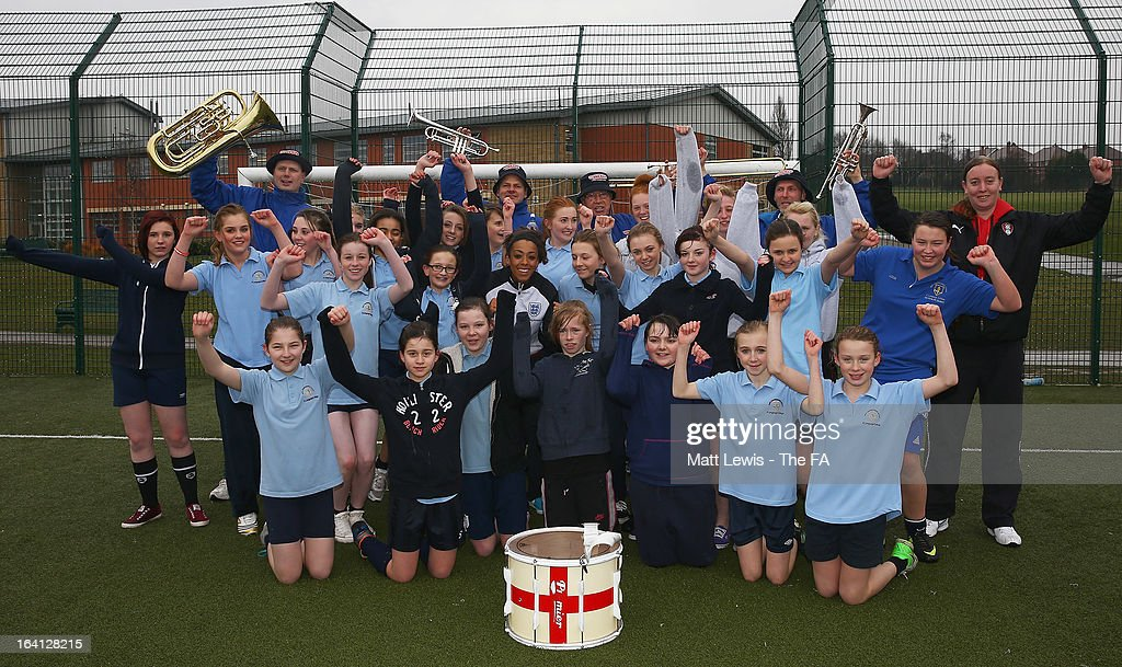 Jess Clarke of England and Lincoln Ladies and the England Band help promote the Womens football match between England and Canada during a School visit to Wath Secondary School on March 20, 2013 in Rotherham, England.