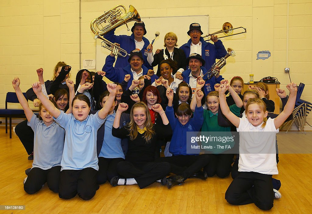 Jess Clarke of England and Lincoln Ladies and the England football band help promote the Womens football match between England and Canada during a School visit to Meadow View Primary School on March 20, 2013 in Rotherham, England.