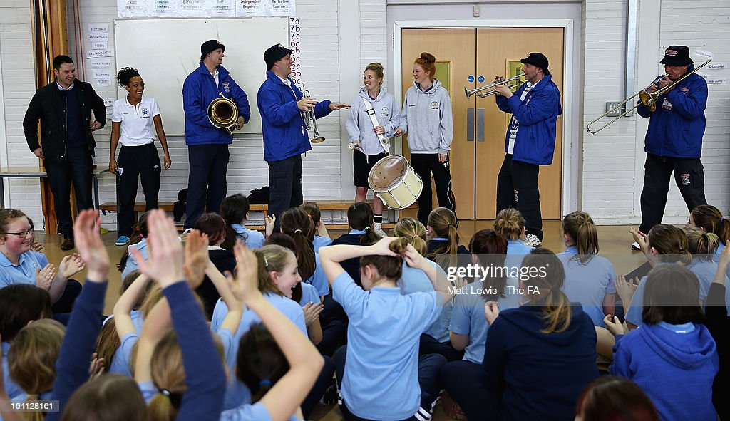 Jess Clarke of England and Lincoln Ladies and the England football band help promote the Womens football match between England and Canada during a School visit to Wath Secondary School on March 20, 2013 in Rotherham, England.
