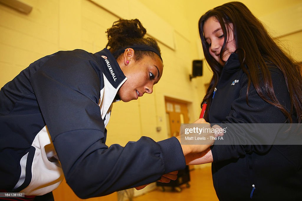 Jess Clarke of England and Lincoln Ladies signs autographs as she helps promote the Womens football match between England and Canada during a School visit to Meadow View Primary School on March 20, 2013 in Rotherham, England.