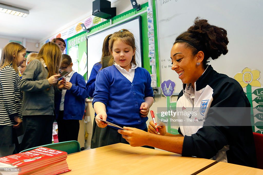 Jess Clarke of England signs autographs to promote the women's football match between England and Canada during a school visit to Wickersley Northfield School on March 28, 2013 in Rotherham, England.