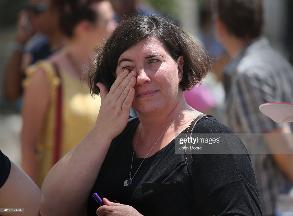 Jess Marke wipes a tear while visiting the Emanuel AME Church with her family, on the one-month anniversary of the mass shooting on July 17, 2015 in Charleston, South Carolina. Visitors from around the nation continue to visit a makeshift shrine in front of the church, in a show of faith and solidarity with 'Mother Emanuel', as the church is known in Charleston. Nine people were allegedly murdered on June 17 by 21-year-old white supremacist Dylann Roof, who was captured by police in North Carolina the following day. He is scheduled to go to trial July 11, 2016.