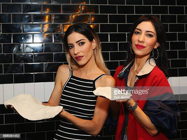 Jess Origliasso and Lisa Origliasso from The Veronicas pose with pizza dough they had been kneading during the launch of Fratelli Famous at Westfield...