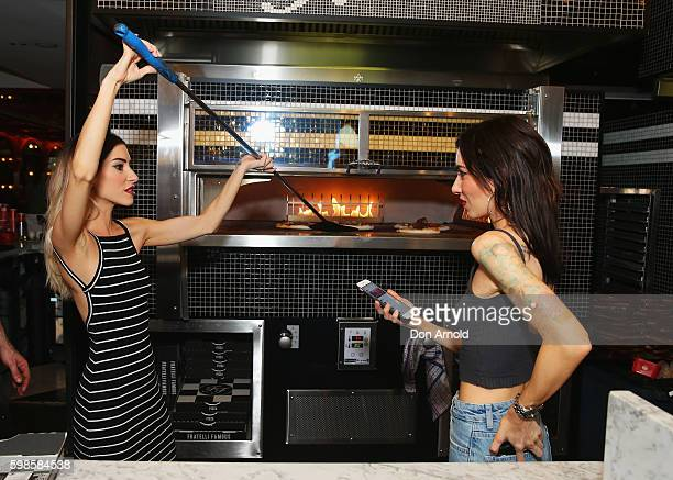 Jess Origliasso attends to a pizza whilst Lisa Origliasso takes a picture of her doing so during the launch of Fratelli Famous at Westfield Sydney on...