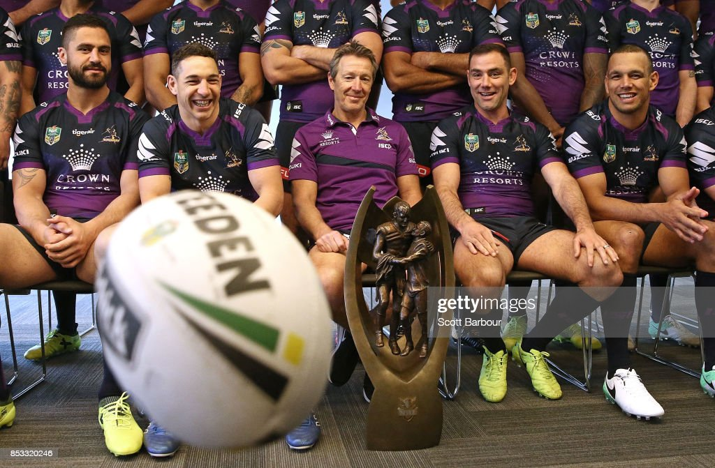 Jesse Bromwich, Billy Slater, coach Craig Bellamy, captain Cameron Smith and Will Chambers watch as a ball bounces as they pose for their team photo with the Provan-Summons trophy during a Melbourne Storm NRL training session at Gosch's Paddock on September 25, 2017 in Melbourne, Australia.