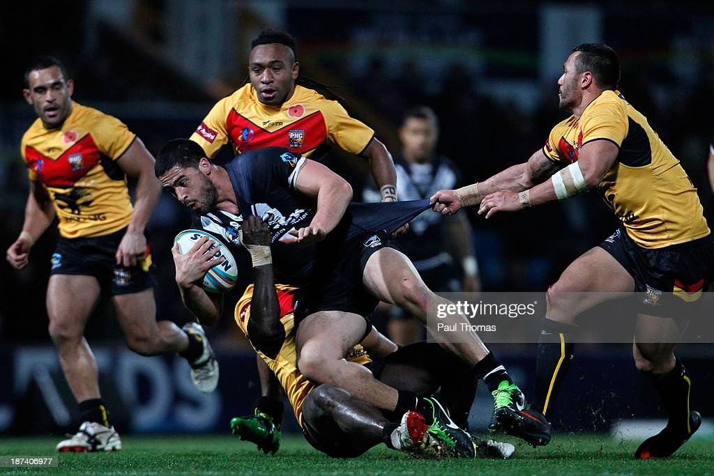 Jesse Bromwich (C) of New Zealand is tackled by Jason Chan (R) and Joe Bruno of Papua New Guinea during the Rugby League World Cup Group B match at Headingley Stadium on November 8, 2013 in Leeds, England.